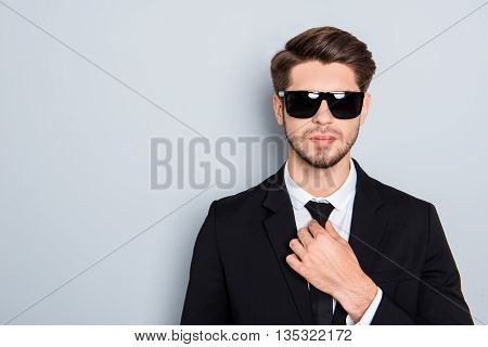 Portrait Of Young Successful Man In Glasses Correcting Tie