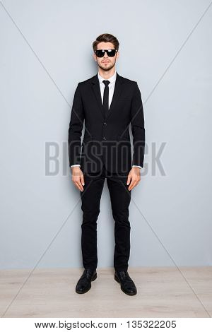 Full Length Portrait Of Handsome Businessman In Black Suit And Spectacles