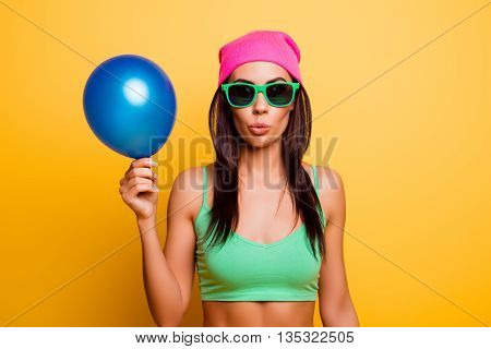 Cheerful Hipster Girl In Pink Hat  Holding Balloon On Yellow Wall