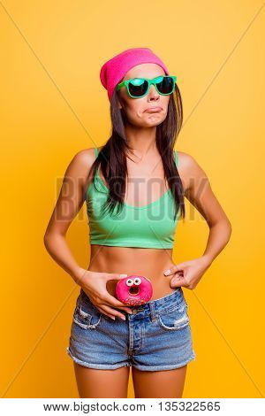 Sad Hipster Girl  Holding Pink Donut Near Her Belly, She Afraid To Be Fat