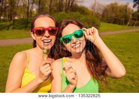 Portrait Of Two Sexy Girls In Glasses Holding Lollipops