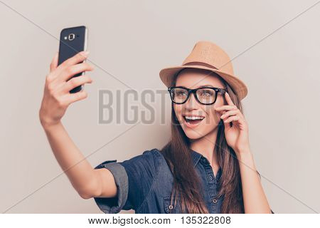 Cheerful Girl In Cap And Glasses Making Selfie On Smartphone