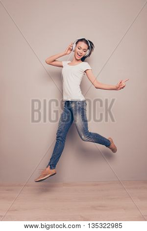 Young Positive Happy Girl Jumping While Listening Music