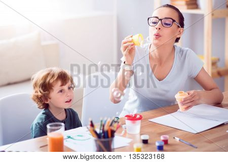 Thats cool. Young energetic mother blowing soap bubbles while sitting with her little charmed son at the table