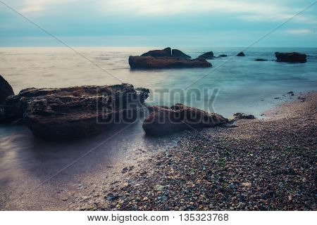 Sea coast with rocks, soft water and cloudy sky, natural seasonal summer background with long exposure