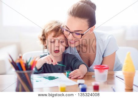 What a wonderful color. Concentrated little charming boy painting while his mother hugging him
