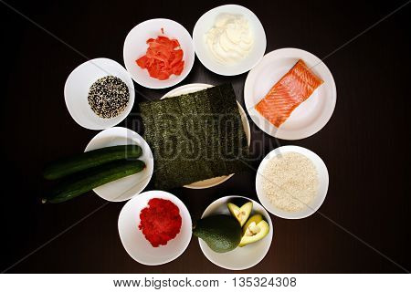 Table served with Ingredients of sushi in plates on dark background. rice with vegetables, nigiri, soy sauce, cucumber, salmon, avocado, caviar, nori, sesame. Before to be a roll. Top view