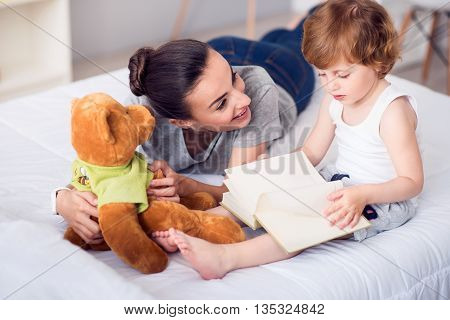 Time for a story. Surprised young mother lying on the bed while her son sitting and turning pages in the book