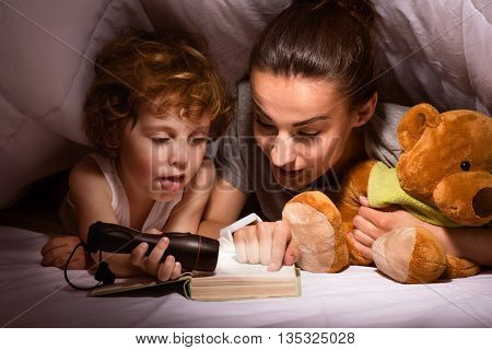 Bedtime story. Young modern mother reading a tale to her son using a flashlight in a hut of blankets