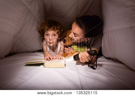 Our secret place. Cute little boy reading a story with his mother and using a flashlight in their hut of blankets