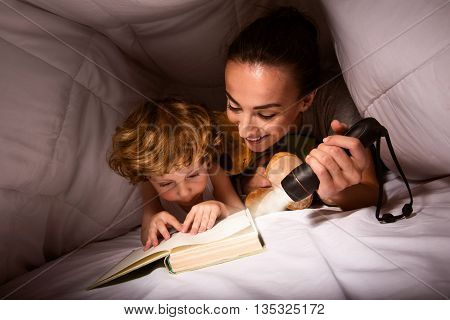 Adventure story. Amazing little boy lying on the bed with his mother and reading a story in a hut of blankets