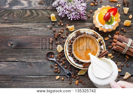 Rustic wooden background with cup of coffee milk fruit tart and lilac flowers. White vintage dinnerware and spoon. Breakfast at summer morning. Top view place for text.