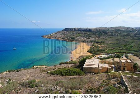 View over Ramla Bay from the Calypso's Cave. The dark blue line extending into the sea off the eastern headland of the bay is an artificial reef which formed a part of the defences built by the Knights of St John to prevent attackers landing on the beach.