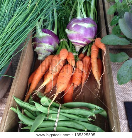 Organic vegetables in a wooden box at a farmers market, with purple kohlrabi, carrots and green beans.
