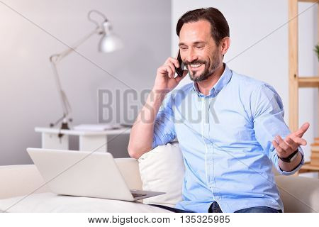 Can not believe it. Delighted man talking on the phone and getting good news while sitting in front of the laptop