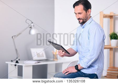 Nice day. Delighted bearded man looking with attention at the tablet in his hands while sitting on the back of a couch