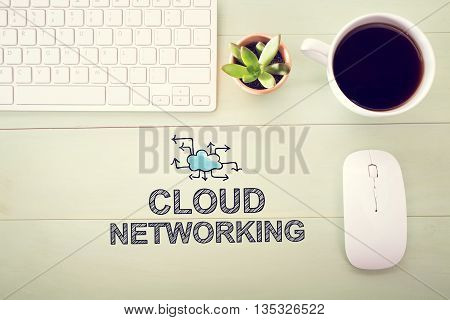 Cloud Networking concept with workstation on a light green wooden desk