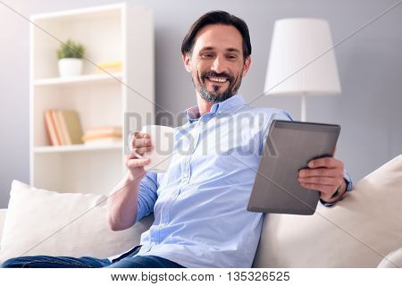 Some relaxation. Pleasant bearded man looking at the tablet while sitting on the couch and holding a cup of coffee