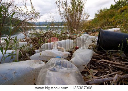 A huge pile of plastic garbage of all sorts in the river, ecology issue.