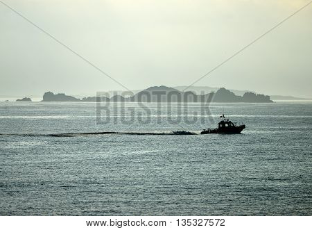 Small boat sailing past rocky islands in mist
