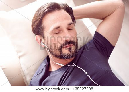 Desired rest. Mature bearded man lying on the couch and sleeping while listening to music through earphones