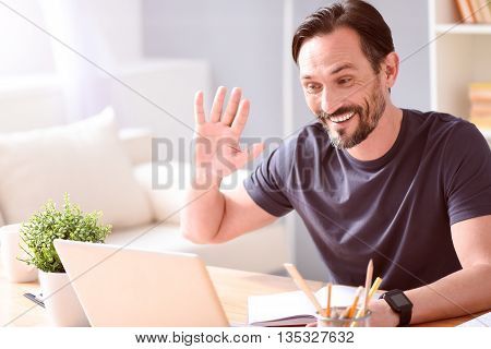 Hey you. Pleasant amiable mature man chatting on the laptop while sitting at the table at home