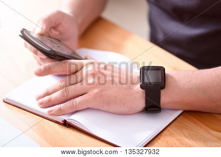 Useful device. Close up of hands of a man holding a smart phone with a chart on the screen while sitting at the table with a notebook on it
