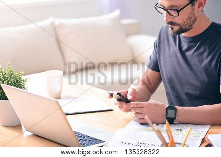 Involved in work. Pensive middle aged man with glasses looking at his phone while sitting at his workplace in front of a laptop