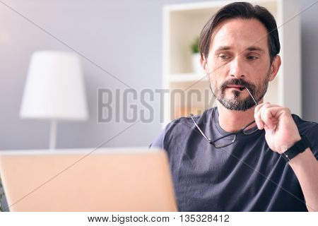 I have to think it over. Thoughtful mature bearded man holding glasses and looking with attention at the computer