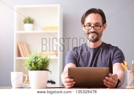 Nice chat., Delighted bearded man smiling and looking at the tablet in his hands while sitting on back of a couch