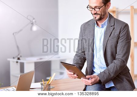 Good job. Handsome mature entrepreneur with glasses smiling while holding a tablet and sitting on the table