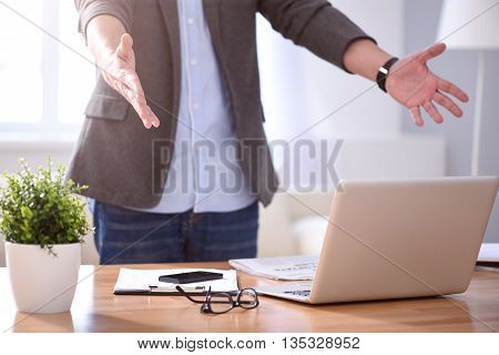 Every day is amazing. Close up of hands of a man standing near his table with open arms