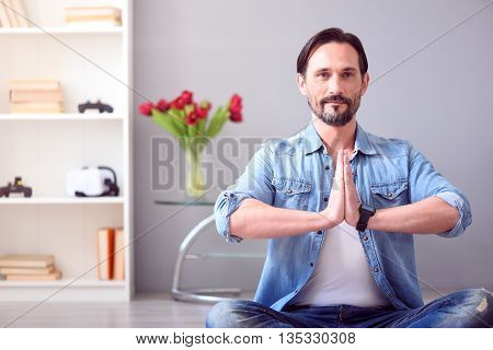 Yoga time. Calm confident middle aged man sitting on the floor in yoga pose and looking in front of him