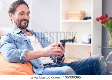 I like good music. Delighted mature bearded man sitting on the bean bag using earphones and looking at his smart phone