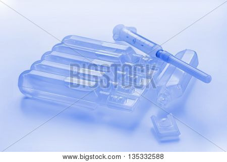 Plastic modern style ampules and syringe. Blue toned still life.