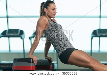 Young Woman Doing Triceps Exercise On Stepper