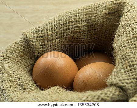 Close Up Three Egg In Sack On Wooden Background