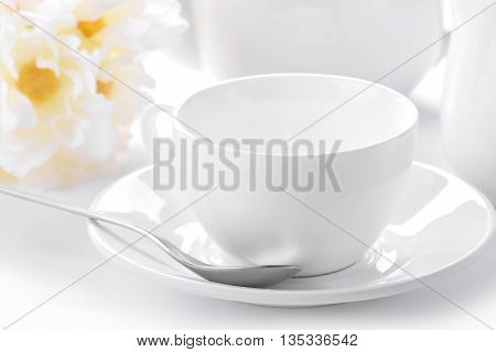 delicate white tea cup and saucer close-up with decorated background