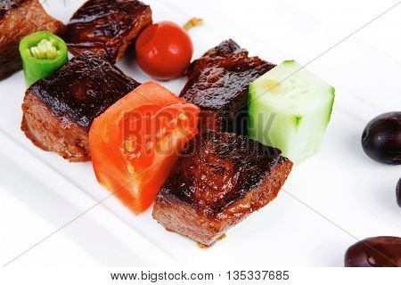 european food: grilled beef meat on white china plate isolated on white background with olives and tomatoes