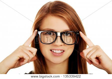Pretty teenage woman improving glasses