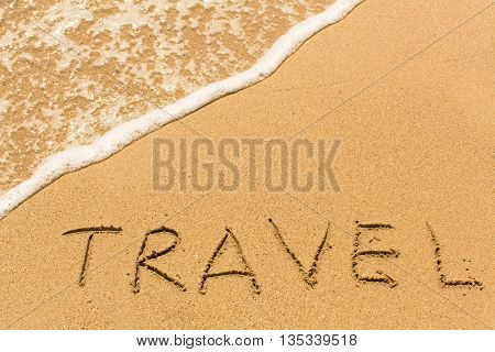 Travel - word drawn on the sand beach with the soft wave.