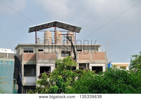 water tank on roof top of the building house under construction.