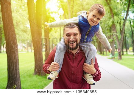 Father is spending sunny day with his small son walking in the park and riding him on shoulders