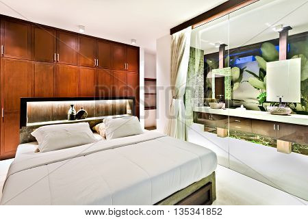 Modern Bedroom With Wooden Cupboards And Glass Wall