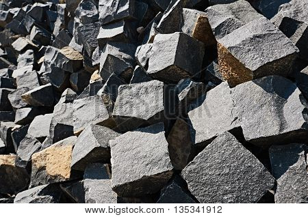 Pavement rocks, stones and cobblestone blocks are in lie in a heap. focus is on foreground