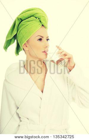 Woman in bathrobe drinks water.