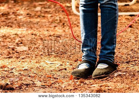 Legs of a girl jumping rope on dry autumn leaves
