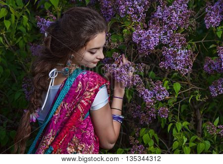 Asian woman dressed in sari in lilac bushes at sunset