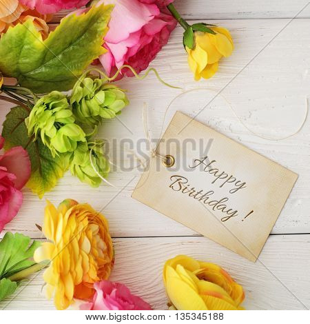 happy birthday greeting card. Gift tag and flowers on white wooden background