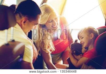 family, transport, safety, road trip and people concept - happy parents with to little girl in baby car seat hugging teddy bear toy
